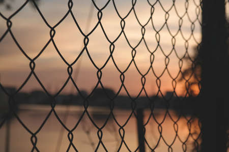 chainlink fence: chain-link fence with sunset light in blurred background