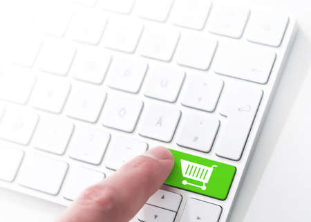 finger pressing a green key with shopping cart symbol on a computer keyboard, concept for e-commerce