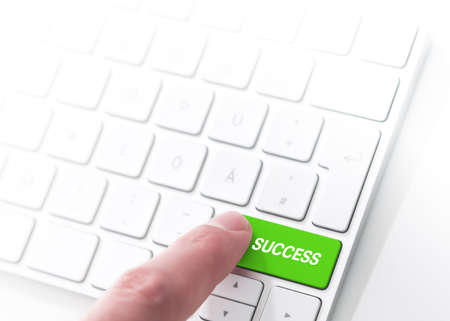 finger pressing a green key labeled SUCCESS on a computer keyboard, key to success