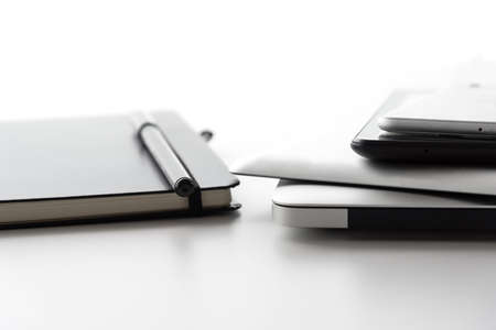 reachability: laptop computer, tablets and mobile phone besides notebook journal and black pen on white desktop surface