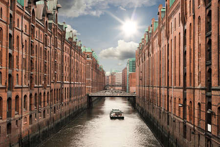 boat on a channel in the old warehouse district Speicherstadt in Hamburg, Germany under sunny blue sky Stock Photo