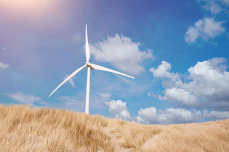 wind turbine behind dunes covered with marram grass under blue summer sky Stock Photo