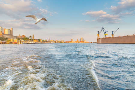 Hamburg cityscape seen from a boat on the river Elbe under beautiful summer sky