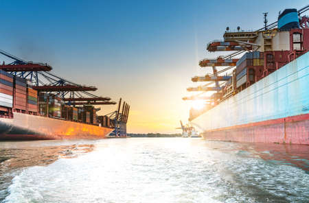 large container ships in harbor at sunset Stock Photo