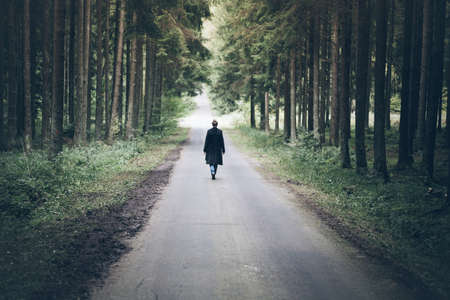 young blonde caucasian woman walking on narrow road through dark forest Stock Photo