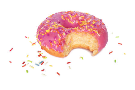 One bite missing of donut with pink frosting and colorful sugar sprinkles isolated on white background