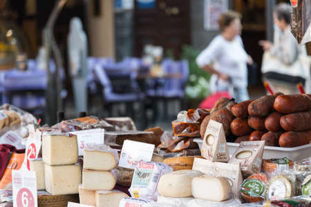 Soller, Spain 10.29.2016: assortment of cheese and sausages at market stall wirh people in shallow background Redakční