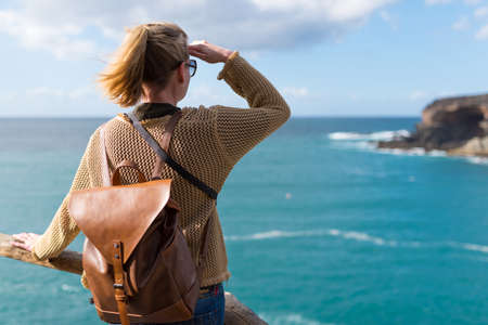 back view of young blonde woman in casual clothes and with leather backpack standing on cliff above ocean shielding her eyes with hand from sunlight
