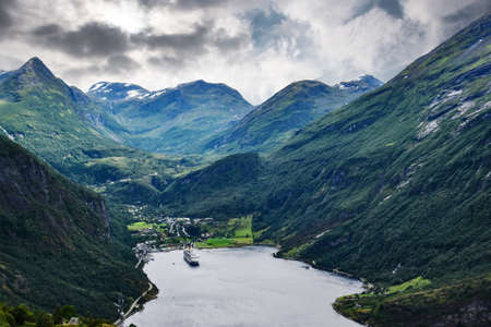 High angle view of large cruise ship anchoring in fjord Geirangerfjorden of Norwegian coast under overcast sky