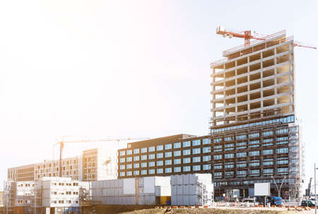 construction site with cranes and half finished buildings on sunny day Stok Fotoğraf