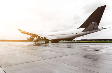 large passenger airplane on airport taxiway on overcast day Stock Photo