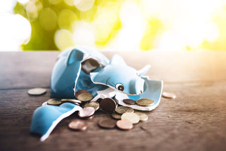 closeup of shattered broken piggy bank with coins on rustic wooden table finance concept
