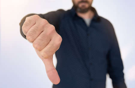 close-up of businessman in blue shirt showing thumbs down gesture, denial concept Stock Photo