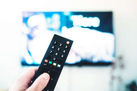 close-up of hand holding remote control against TV on white wall