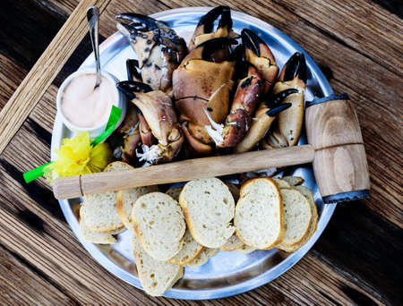 plate with boiled legs and claws of brown crab with bread and dip on rustic wooden table Archivio Fotografico