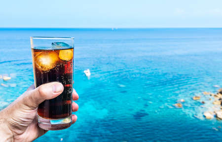 close-up of hand holding drinking glass with ice-cooled cola against blue sky and sea Stock fotó