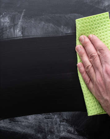 close-up of hand of person cleaning dirty chalkboard with sponge cloth Stockfoto - 115627213