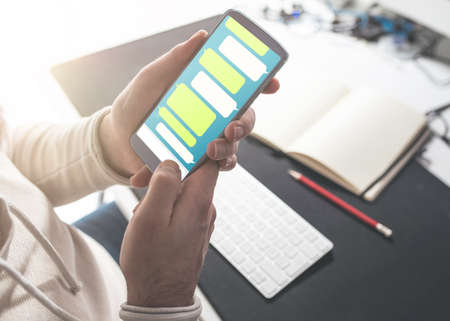 close-up of person using messaging app mock-up on smartphone at office desk