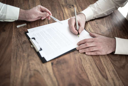 close-up of man signing contract at wooden desk with other person pointing at document