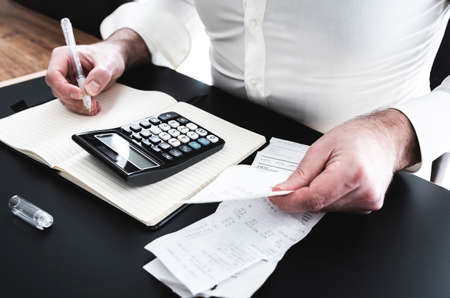 finance concept with man at desk with calculator, bills or sales slips and notpad Stock Photo