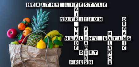 healthy eating wordcloud or crossword with variety of fresh fruits in brown paper bag
