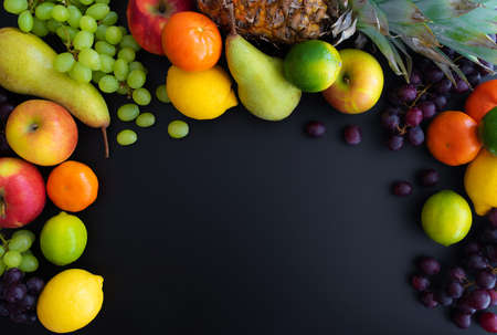 different fresh healthy fruits on black background Stockfoto