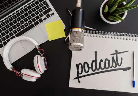 Podcast-Aufnahmekonzept mit Mikrofon, Kopfhörer und Laptop neben Notizblock