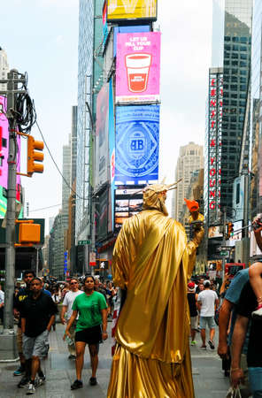 back view of staue of liberty impersonator on crowded street at Times Square