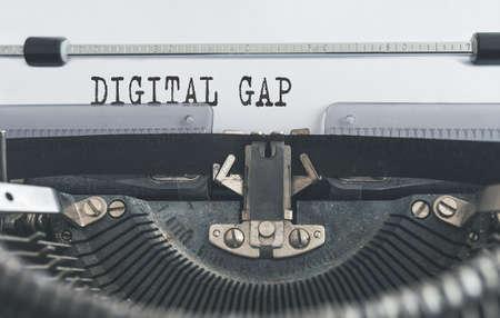words DIGITAL GAP written on old manual typewriter