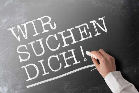 ręka trzymająca kawałek kredy pisząca słowa WIR SUCHEN DICH, po niemiecku, bo szukamy Ciebie lub chcemy Ciebie, oferta pracy i koncepcja możliwości