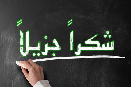 Arabic words shukraan jazilaan in Arabic script meaning thank you very much on blackboard Stok Fotoğraf