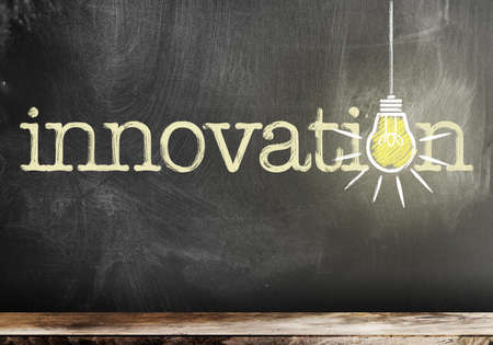 word innovation on chalkboard with glowing light bulb symbolizing and idea