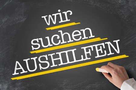 text WIR SUCHEN AUSHILFEN, German for Help Wanted, written on blackboard with hand holding piece of chalk