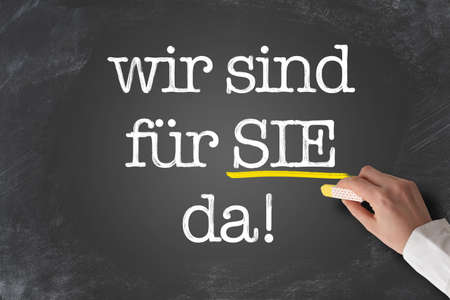 text WIR SIND FÃœR SIE DA, German for we are here to assist you, or we are there for you, written on blackboard