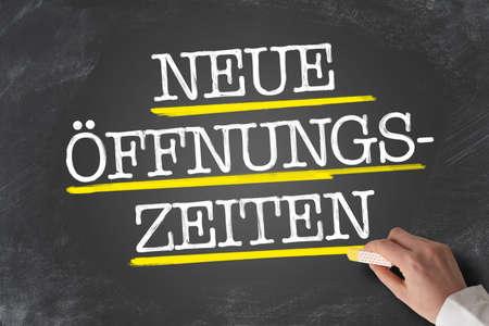 text NEUE ÖFFNUNGSZEITEN, German for new opening hours or changed business hours, written on blackboard Stockfoto