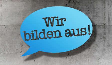 text WIR BILDEN AUS, German for we train apprentices, in speech bubble against concrete wall
