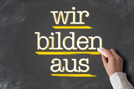 text WIR BILDEN AUS, German for we train apprentices, written on blackboard