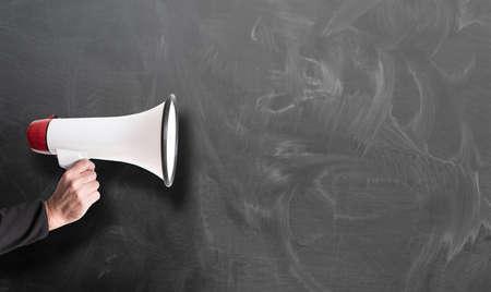 mano que sostiene el megáfono rojo y blanco contra la plantilla de pizarra