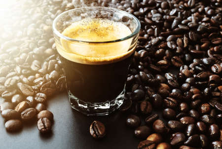 glass filled with dark  hot espresso coffee and roasted coffee beans on table