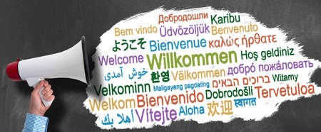 hand of businessman holding megaphone or bullhorn against blackboard with word WELCOME in different languages