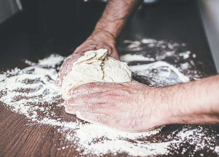 close-up of hands of man kneading yeast dough on floured kitchen counter