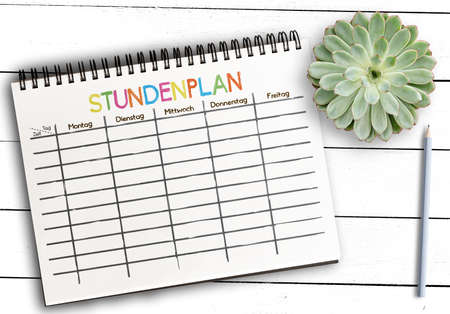 top view of class schedule or timetable template with German word STUNDENPLAN on notepad against rustic white wooden table