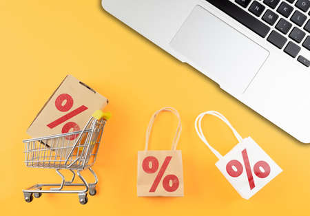 online shopping and e-commerce concept with shopping cart and laptop computer on orange desk Stok Fotoğraf