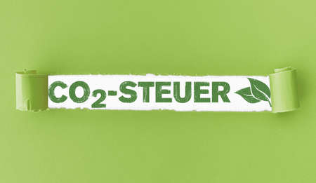 torn paper with text CO2-Steuer, German for Carbon Tax, and green leaves in opening