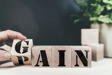 changing word PAIN to GAIN on wooden blocks, no pain no gain success concept Imagens