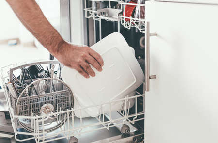 close-up of person emptying or loading dishwasher in kitchen Stock fotó