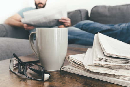 man relaxing on sofa reading a newspaper with stack of newspapers and coffee mug in foreground