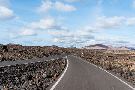 empty asphalt road road through arid volcanic landscape against blue sky Фото со стока
