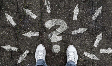 person standing on road with question mark and arrow markings pointing in different directions, decision making concept
