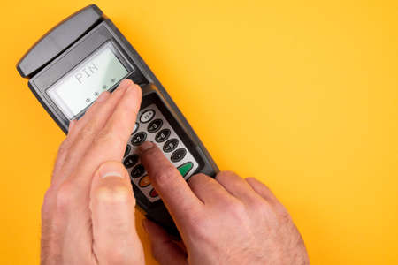 person typing in PIN at POS payment terminal while covering keypad with free hand to prevent spying out of personal data